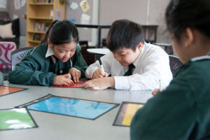 Students work on math problems at St Peter Chanel Catholic Primary School Regents Park