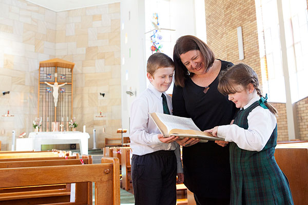 Mother and her two children reading the bible together inside the St Peter Chanel Catholic church