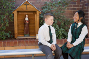 Students sitting on a bench and chatting at St Peter Chanel Catholic Primary School Regents Park