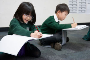 Two kindergarten students learning to write at St Peter Chanel Catholic Primary School Regents Park