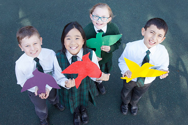 Four students at St Peter Chanel Catholic Primary School Regents Park holding sybols of school values
