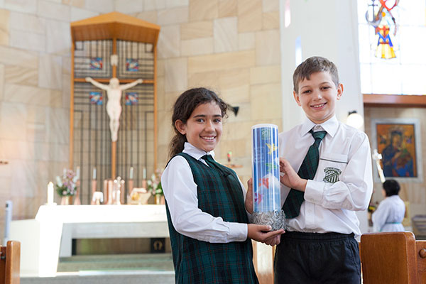 Two students holding their St Peter Chanel Catholic Primary School Regents Park school candle inside the church