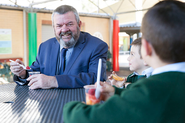St Peter Chanel Catholic Primary School Regents Park principal sitting and enjoying breakfast with students in the playground