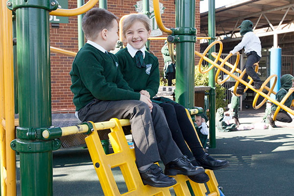 Two students at St Peter Chanel Catholic Primary School Regents Park sitting and talking on play equipment